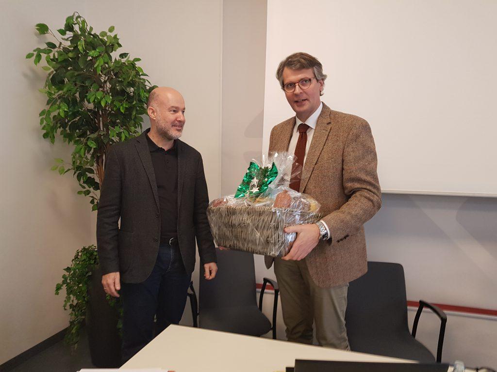Präsident Sucher überreicht dem Geschäftsführer Erler auf der Vollversammlung der LAK einen Dankeskorb.
